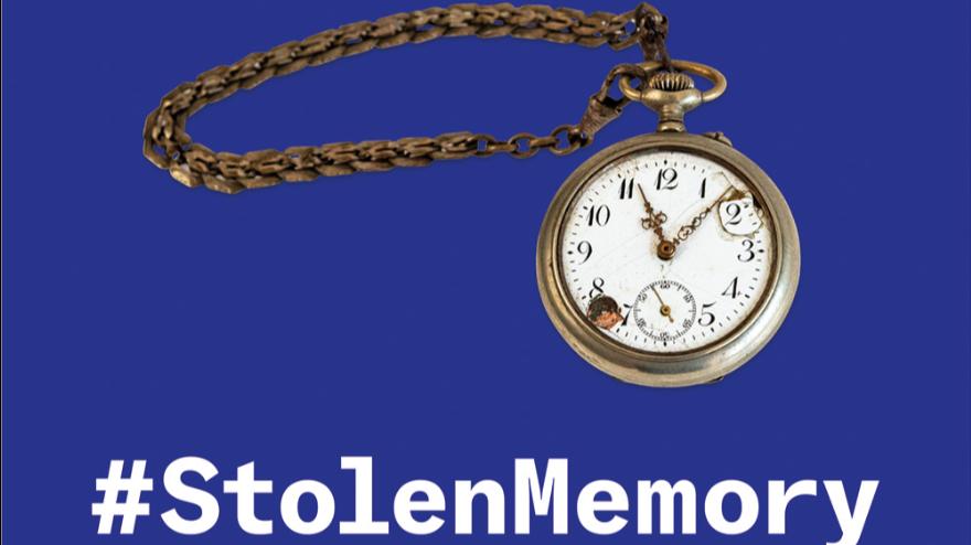 złoty zegarek na łańcuszku na fioletowym tle, na środku biały napis: #StolenMemory, na dole opis wystawy drobnym drukiem